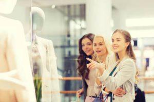 La vente, la consommation et les gens notion - heureux jeunes femmes avec des sacs pointant le doigt pour faire du shopping fenêtre dans centre commercial Banque d'images - 47664037